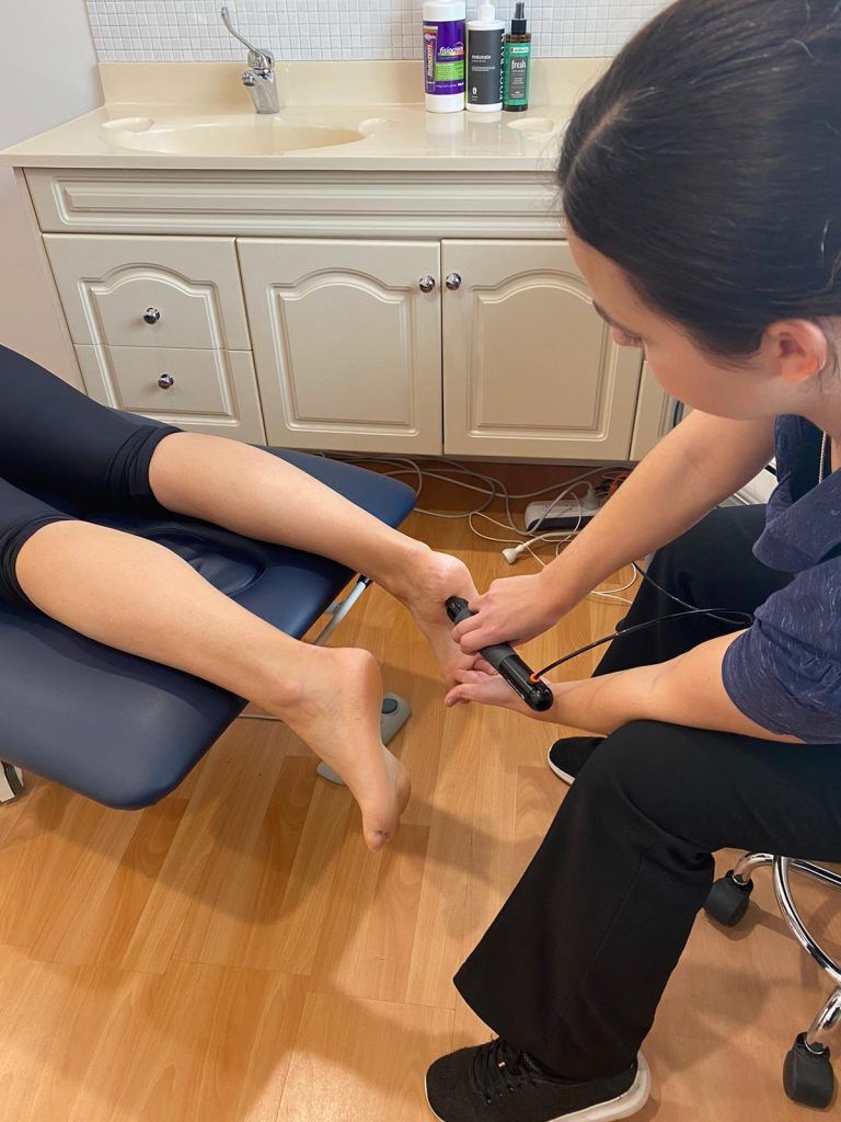 Podiatrist using shockwave therapy to treat a patient