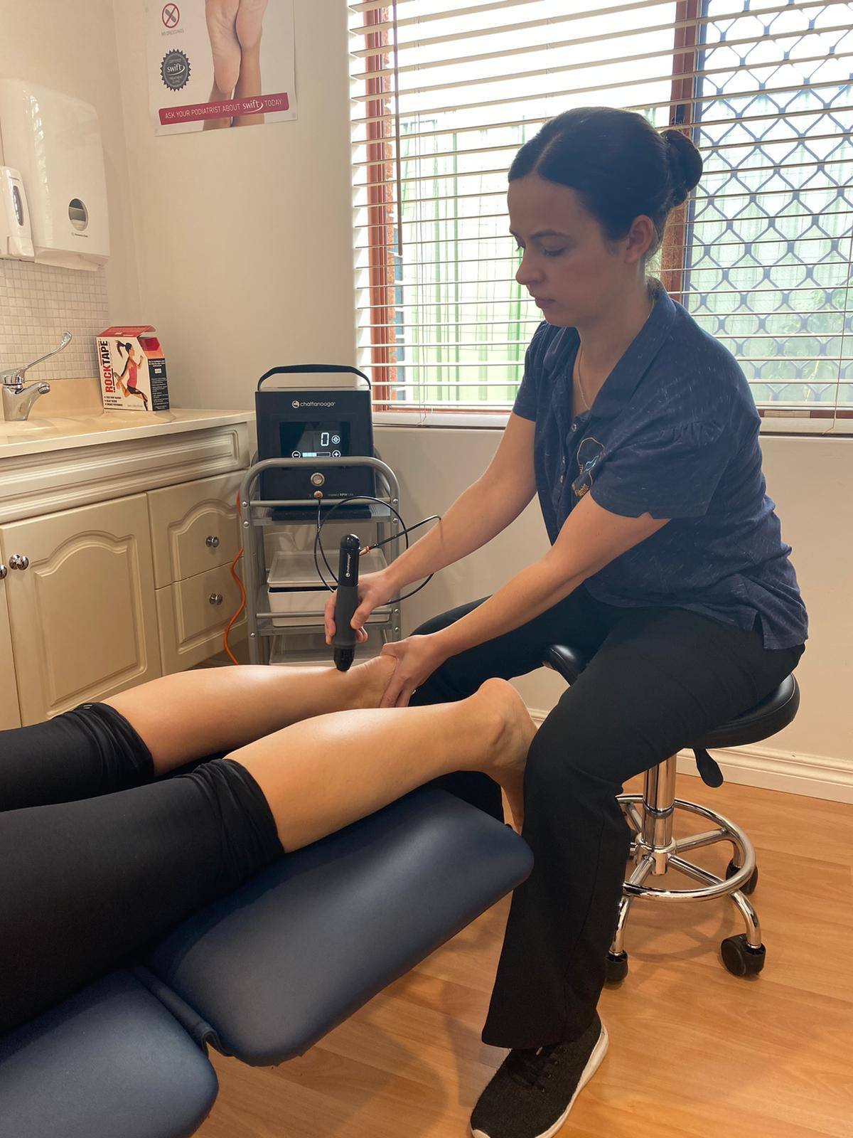 Podiatrist treating patient using shockwave therapy